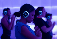 women wearing headphones while doing yoga